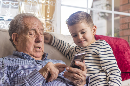 Grandfather and grandson looking a smart phone at home Poster