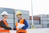 Fototapety Workers shaking hands in shipping yard