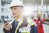 Fototapety Male worker using walkie-talkie with colleague in background at shipping yard