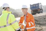 Fototapety Happy engineer discussing with colleague at construction site on sunny day