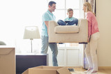 Fototapety Parents carrying son on armchair in new house