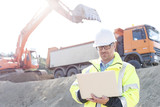 Fototapety Supervisor using laptop at construction site on sunny day