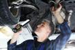Mechanik, mężczyzna naprawia samochód.Samochód w warsztacie, mechanik sprawdza stan podwozia.