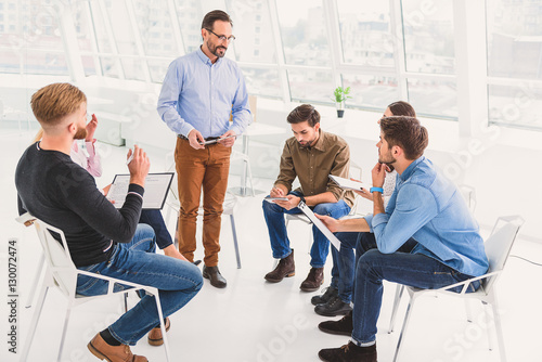 Poster Smiling psychologist making conversation with group