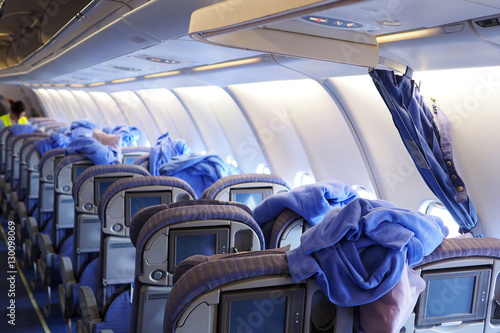 Cleaning staffs clean the airplane cabin including blankets, pillows and passenger seats Poster