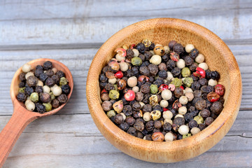 Bowl and spoon with colorful peppercorns