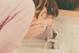 Woman washing face in bathroom. Hygiene.