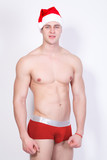 young handsome sexy macho christmas man in red santa claus hat and red underwear with muscular bare torso in xmas holiday for new year celebration on white background
