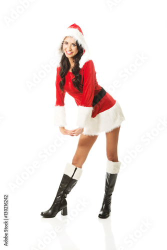 Attractive santa woman standing astride and inclined, looking to the camera Poster