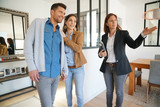 Fototapety Couple with real-estate agent visiting house for sale