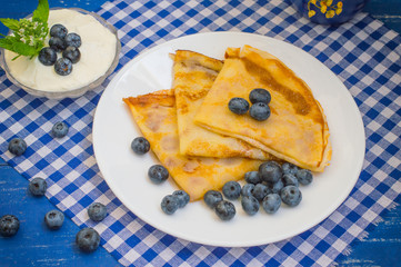 Pancakes with blueberries, whipped cream and a sprig of mint  lemon balm. Wooden blue background. Close-up.