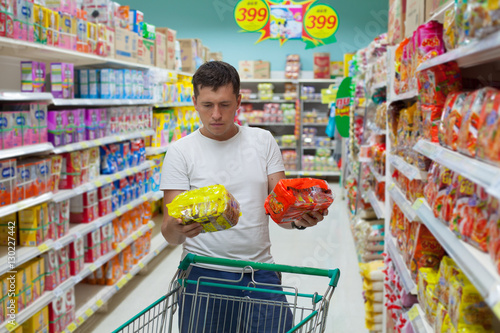 Young caucasian man make choose between two similar goods. Shopping in supermarket or grocery