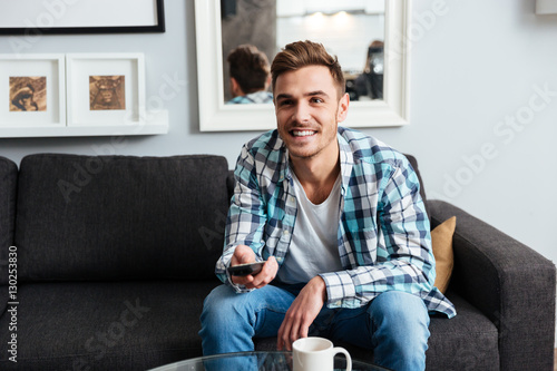 Poster Joyful young bristle man holding remote control while watching TV