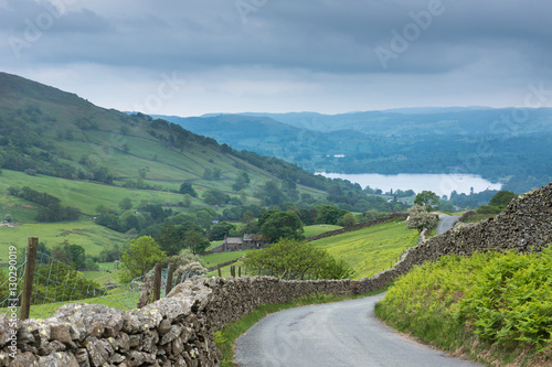 Lake District, England - May 30, 2012: Rural road with stone walls on the side meanders through the landscape. Shot from above shows lake downhill. Green meadows, forests and ferns
