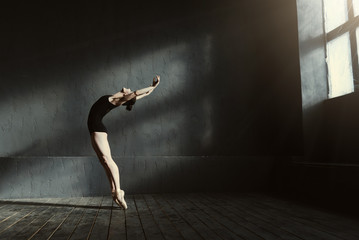 Flexible ballet dancer stretching in the dark lighted studio