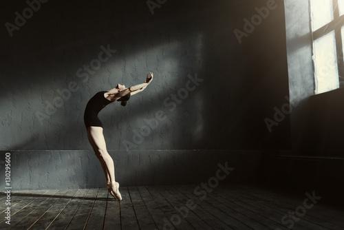 Plakat Flexible ballet dancer stretching in the dark lighted studio