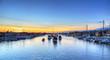 Balboa Island harbor at sunset with ships and sailboats visible from the bridge that leads into Balboa Island, Southern California, USA