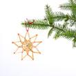 halm stjärna hänger i julgran med vit bakgrund
