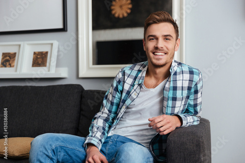 Poster Happy young man sitting on sofa in home