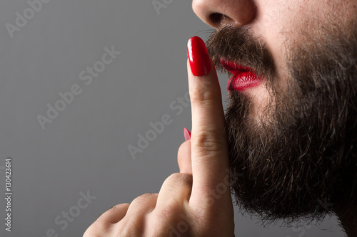 Bearded Man with Red Lipstick on His Lips and Nail Polish Making Silence Gesture Plakat