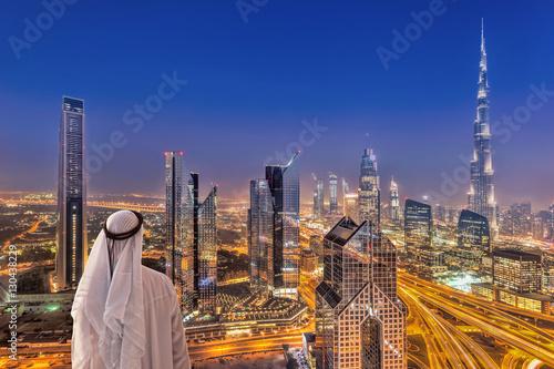 Papiers peints Dubai Arabian man watching night cityscape of Dubai with modern futuristic architecture in United Arab Emirates