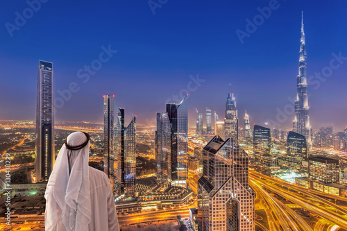 Arabian man watching night cityscape of Dubai with modern futuristic architectur Poster