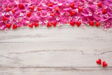 Wooden background with rose petals and hearts