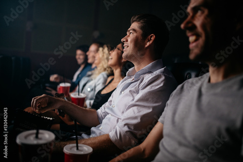 People sitting in cinema hall watching movie