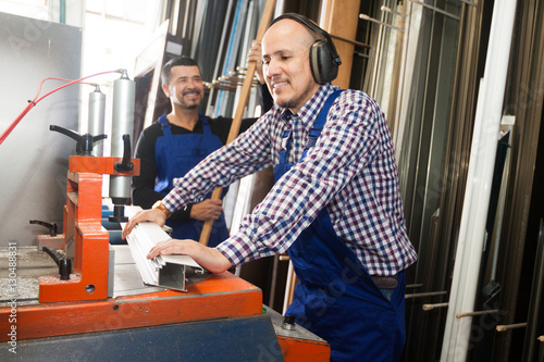workmen near cutter - lathe machine at factory v