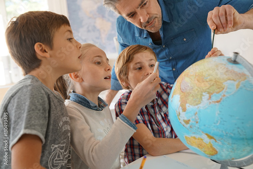 Plagát Teacher with kids in geography class looking at globe
