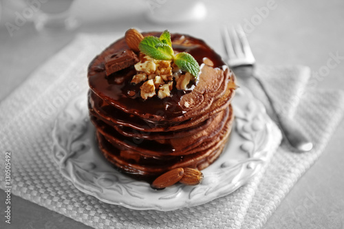 Foto op Canvas Chocolade Tasty pancakes with nuts and chocolate sauce on plate