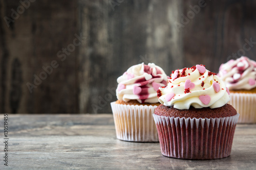 Poster Valentine cupcakes decorated with sweet hearts on wooden table