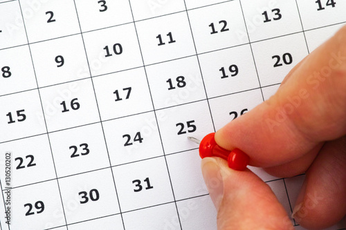 Poster Person hand putting pin on number 25 in calendar