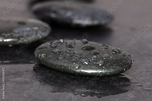 Spa background. Volcanic rocks on reflective background with raindrops. Relaxation, body care treatment, spa, wellness concept