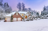 Driveway view of snowy home - daylight fades over a snow-covered suburban home - 130572275