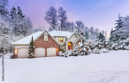 Foto Murales Driveway view of snowy home - daylight fades over a snow-covered suburban home