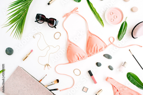 female summer bikini swimsuit and accessories collage on white with palm branches, necklace and sunglasses. flat lay, top view