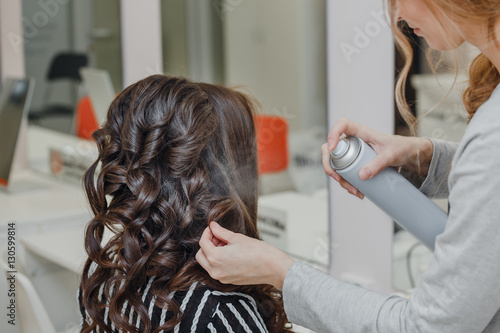Stylist curling hair and making wedding hairstyle for brown haired woman Poster