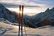 tra i due sci,si vede il tramonto del sole dietro le montagne del monte Bianco