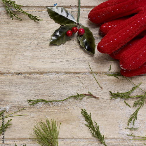 Poster red gloves and holly on a wooden surface