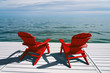 Red Muskoka or Adirondack Chairs on a dock overlooking the water with blue sky