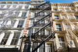 Building facades with fire escape stairs, sunny day in Soho, New York - 130670058