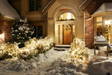 Christmas decorations and lights line front path and patio in the snow - 130673019