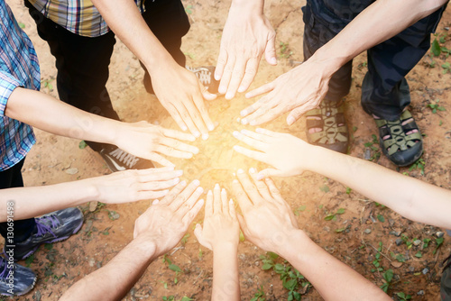 Posting back hand to the center of group of people in circle to