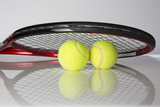Tennis racket and two balls for playing tennis on a black background