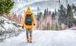 traveler with a backpack walking on snow covered road in winter forest