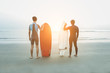 Young surfers waiting the waves on beach with back sunlight