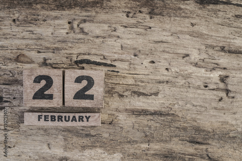 Poster cube calendar for february on wooden background