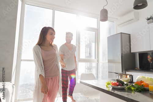 Poster Young Couple Holding Hands In Kitchen, Asian Woman Leading Hispanic Man Modern A