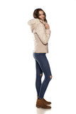 profile of young woman in a winter jacket and jeans on the white background